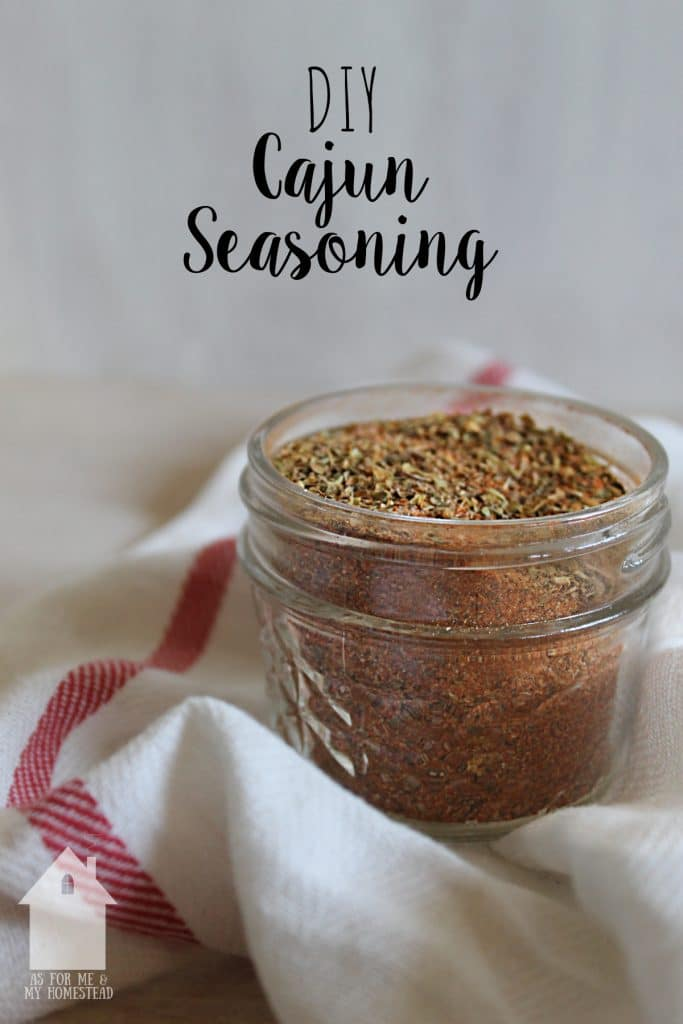 DIY Cajun Seasoning in a small glass jar atop a red-striped white cloth