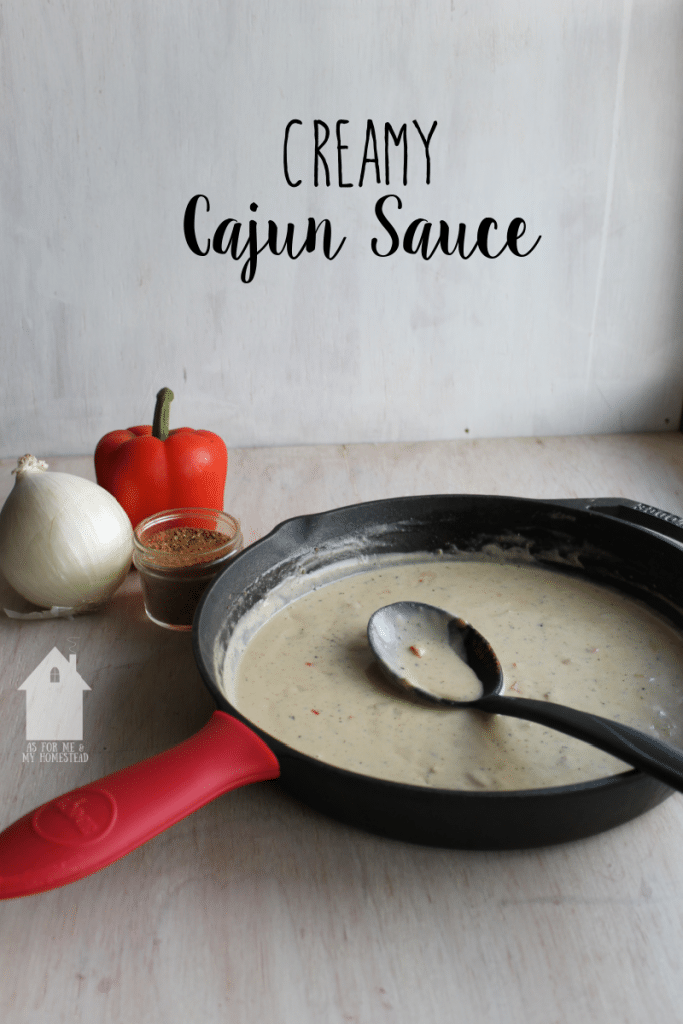 A Lodge skillet full of creamy cajun sauce, with an onion and red pepper beside it.